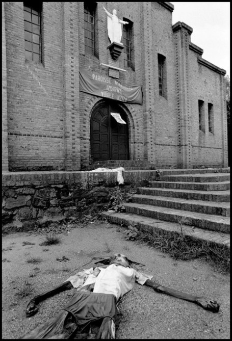 RWANDA. 1994. As a harbinger of the slaughter inside, a decaying corpse lies in front of the entrance of the parish church of Nyarubuye. Over 1000 refugees, perhaps as many as 5000, were killed in the seminary.
